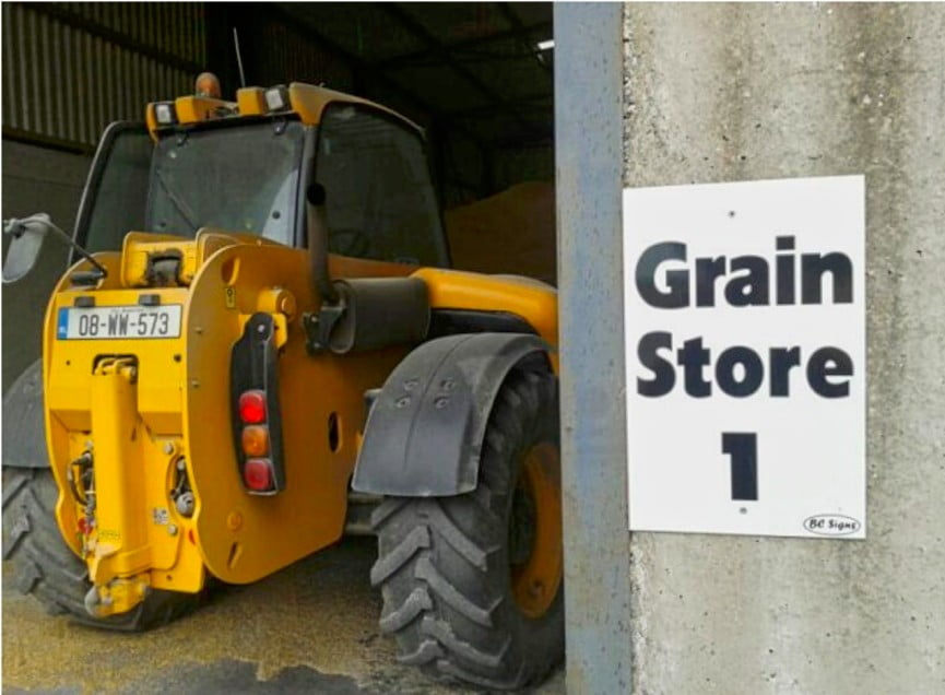 yellow-farm-equipment-parked-in-grain-store
