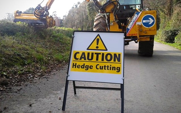 a temporary hedge cutting sign on the side of the road
