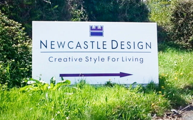 newcastle design shop directions sign on the side of the road