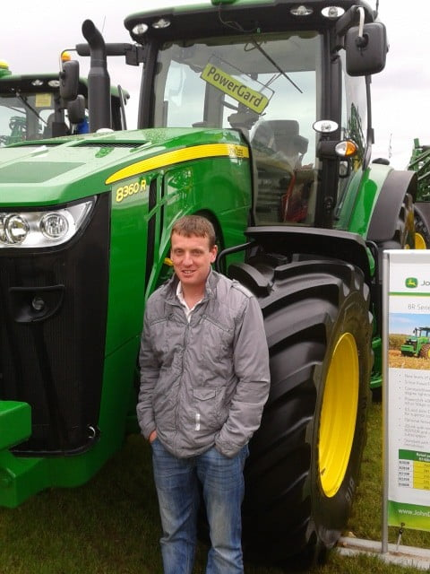 a photo of brian carey standing next to a green tractor